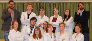 En gruppe elever og to underviserer står i vide kapper