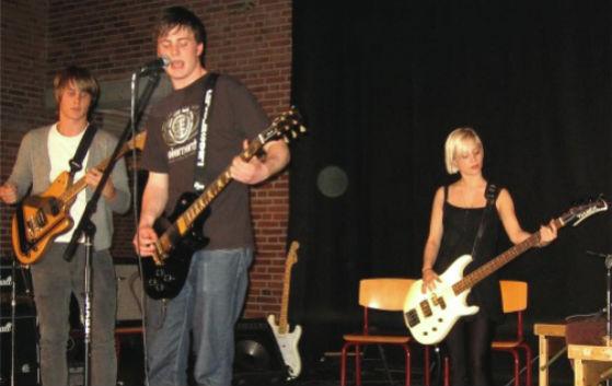 3 studerende optræder med instrumenter på en scene
