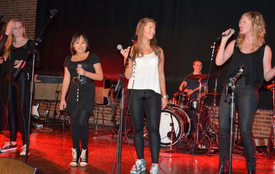 4 piger synger på en scene
