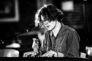 Ung mand der spiller klaver g synger
