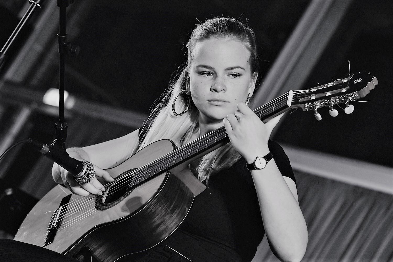 Ung pige som spiller guitar
