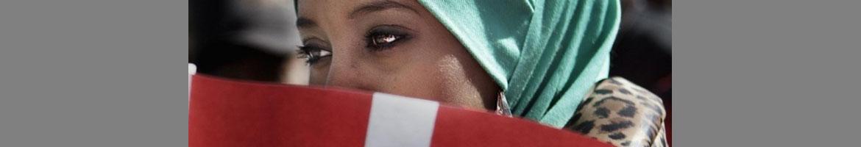 Kvinde med tørklæde holder dansk flag foran sig